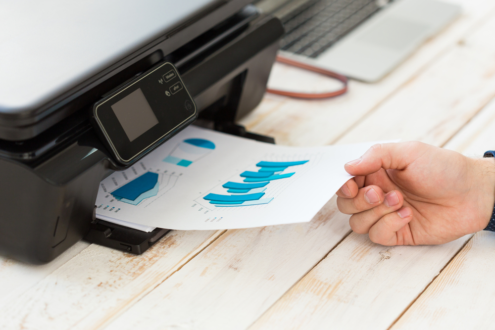 hand taking printing paper from printer